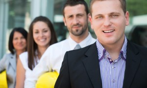 Executive man posing with colleagues in front of modern building